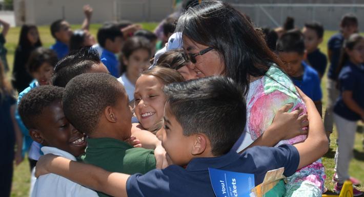 Students hug a teacher