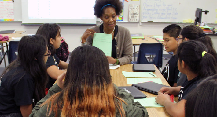A teacher instructs a table full of students